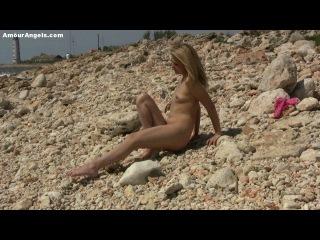 Красивая блондинка играет со своей киской на берегу моря